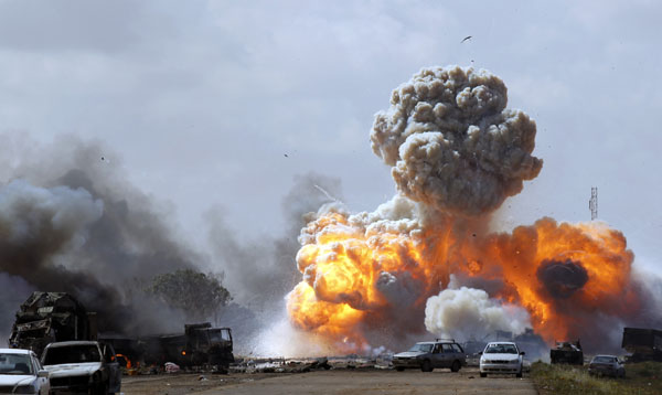 Vehicles belonging to forces loyal to Libyan leader Muammar Gaddafi explode after an air strike by coalition forces, along a road between Benghazi and Ajdabiyah
