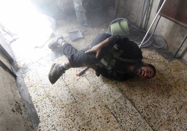 A Free Syrian Army fighter screams in pain after he was injured in his leg by shrapnel from a shell fired from a Syrian Army tank in the Salaheddine neighbourhood of central Aleppo
