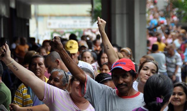 Venezolanos hacen colas en comercios en la búsqueda del