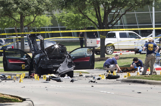 Local police and FBI investigators collect evidence, including a rifle, where two gunmen were shot dead after their bodies were removed in Garland