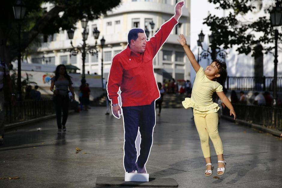 a-girls-jumps-next-to-a-picture-of-late-venezuela-s-president-hugo-chavez-at-plaza-bolivar-in-caracas