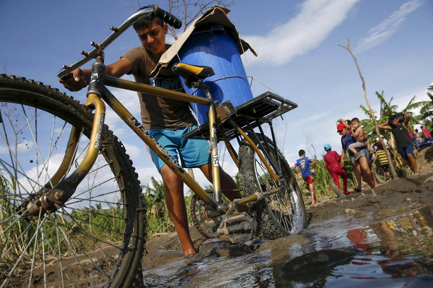 A boy pushes his bicycle loaded with a bucket across a dirt track next to people carrying their belongings, across to Colombia through the Tachira river at San Antonio in Tachira state, Venezuela