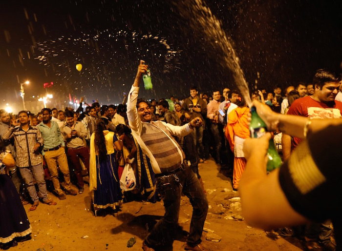 People dance during the New Year's celebrations on a beach in Mumbai