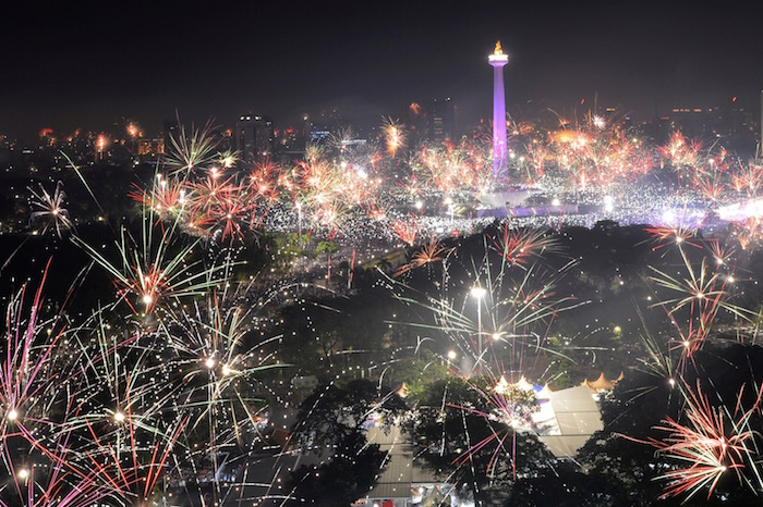 Fireworks explode around National Monument during New Year celebration in Jakarta
